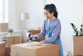 young woman moving out, packing boxes